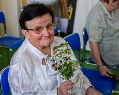 Seniorka trzyma w dłoni bukiecik z polnych kwiatów. Uśmiecha się. W tle inni seniorzy, krzesła ustawione w rzędy.