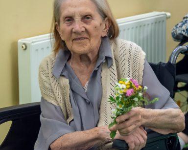 Seniorka trzyma w dłoni bukiecik z polnych kwiatów. Uśmiecha się.