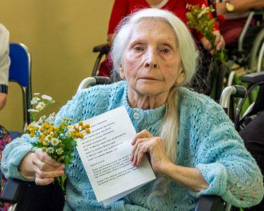 Seniorka trzyma w dłoni bukiecik z polnych kwiatów, w drugiej śpiewnik. Uśmiecha się. Za nią siedzą seniorzy z bukiecikami.