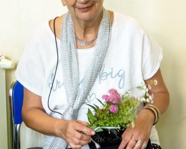Na krześle siedzi seniorka. Trzyma w dłoni bukiecik z polnych kwiatów. Uśmiecha się.