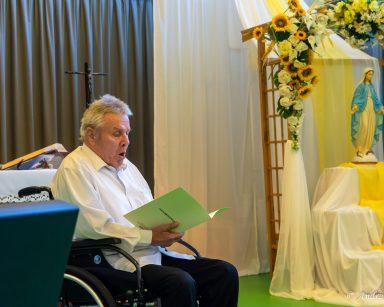 Senior śpiewa psalm. W tle ołtarz, udekorowana białymi i żółtymi kwiatami pergola z figurką Matki Boskiej.
