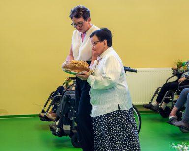 Kierowniczka Mariola Ludwicka i seniorka niosą chleb do poświęcenia. W rzędach siedzą seniorzy z bukiecikami polnych kwiatów.