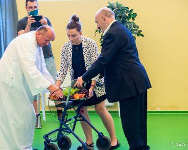 Senior i fizjoterapeutka Martyna Józefczyk przynoszą owoce. Ksiądz Krzysztof Rybka błogosławi dary. Obok administrator Łukasz Cielebański.