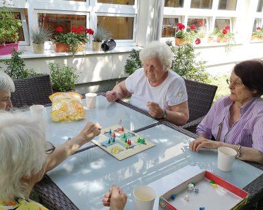 W ogrodzie przy stole cztery seniorki. Grają w grę planszową. Na blacie plansza z pionkami, kostki do gry, kubki z napojem, chrupki.