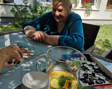 Zielony, zacieniony ogród. Na pierwszym planie dzbanek z lemoniadą na stole. Dalej seniorki grają w warcaby.