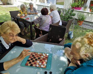 W cieniu drzewa dwie seniorki. Śmieją się i grają w warcaby. Dalej cztery seniorki wspólnie grają w grę planszową.