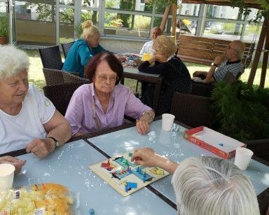 Zielony ogród. W cieniu drzew seniorzy grają przy stołach w gry planszowe i warcaby.