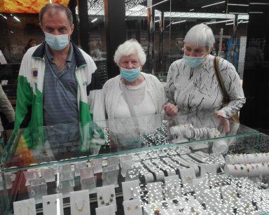 Muzeum Bursztynu. Seniorzy przy szklanej gablocie. Oglądają biżuterię z bursztynami.