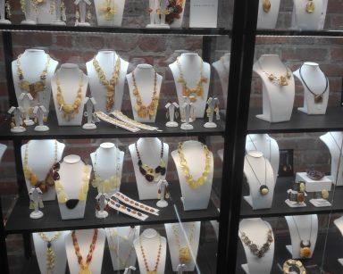 Szklana gablota. W niej wystawione naszyjniki z kawałkami bursztynów, bursztynowe kolczyki i bransoletki.