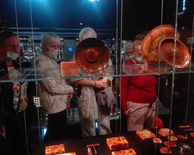 Muzeum Bursztynu. Seniorzy przy szklanej gablocie. Oglądają bursztynowe wyroby. Tace, puzderka, popielniczki, korkociąg.