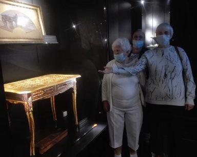 Seniorzy zwiedzają Muzeum Bursztynu. Jedna z seniorek wskazuje ręka bursztynowe biurko.