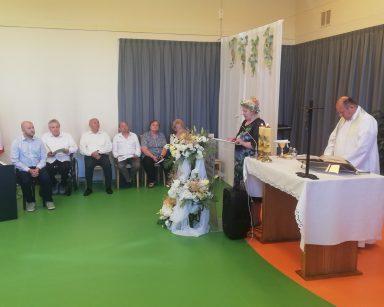Ksiądz proboszcz przy ołtarzu. Obok stoi seniorka w kolorowym wianku czyta. Pod ścianą siedzą seniorzy i kierownik Arkadiusz Wanat.