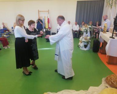 Dyrektorka Agnieszka Cysewska i seniorka podają karafkę z winem księdzu Krzysztofowi Rybce. Wolontariusz Andrzej Zięba robi zdjęcia.