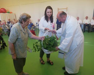 Na sali seniorzy ubrani odświętnie. Fizjoterapeutka Paulina Winczura i seniorka podają kosz z ziołami księdzu Krzysztofowi Rybce.