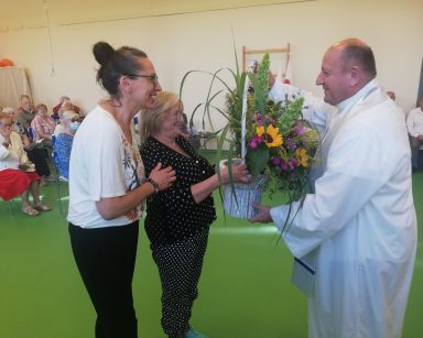 Na sali odświętnie ubrani seniorzy. Terapeutka Magdalena Poraj-Górska i seniorka podają kosz z kwiatami księdzu Krzysztofowi Rybce.