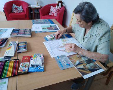 Seniorka siedzi i koloruje obrazek. Na blacie obrazki do kolorowania, obrazy znanych malarzy, kredki, pastele.