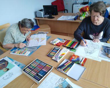 Dwie seniorki kolorują obrazki. Na blacie rozłożone obrazki do kolorowania, obrazy znanych malarzy, kredki, pastele.
