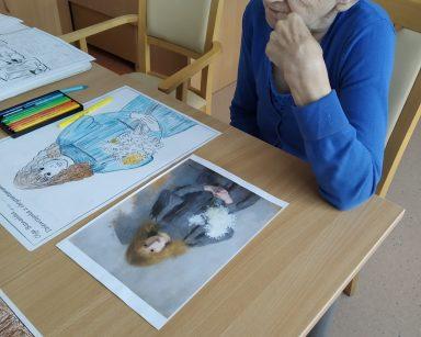 Seniorka siedzi przy stole. Porównuje wykonany obrazek z oryginalnym obrazem.