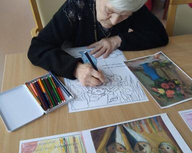 Seniorka koloruje obrazek. Na blacie obrazki do kolorowania, obrazy znanych malarzy, kredki, pastele.