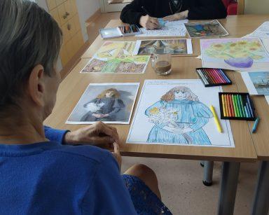 Dwie seniorki kolorują obrazki. Na blacie obrazki do kolorowania, obrazy znanych malarzy, kredki, pastele.