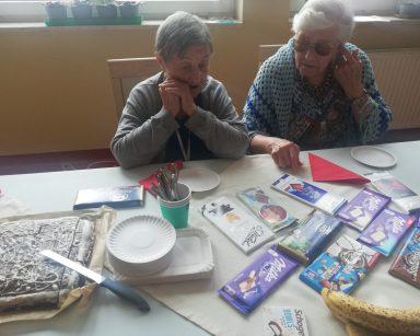 Dwie seniorki przy stole. Na blacie różne czekolady, czekoladowe ciasto, banany, papierowe talerzyki.