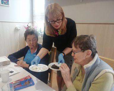 Przy stole dwie seniorki. Dyrektorka Agnieszka Cysewska nachyla się nad nimi i częstuje je czekoladą.
