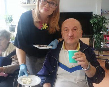 Dyrektorka Agnieszka Cysewska. W dłoniach trzyma talerzyki z czekoladą. Przy stole seniorzy.