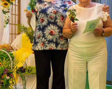 Dwie seniorki. W dłoniach trzymają bukieciki z polnych kwiatów. Za nimi udekorowana kwiatami pergola z figurką Matki Boskiej.