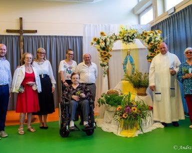 Ksiądz Krzysztof Rybka, dyrektorka Agnieszka Cysewska, seniorzy, pracownicy przy ozdobionej kwiatami pergoli z figurką Maryi.