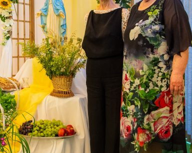 Dwie seniorki przy pergoli ozdobionej białymi i żółtymi kwiatami. Na podwyższeniu figurka Matki Boskiej. Poniżej kosze i tace z darami.
