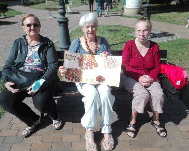 Seniorki odpoczywają na ławce przed Muzeum Bursztynu. Seniorka siedząca w środku trzyma rozłożoną broszurę o bursztynach.