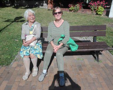 Seniorka i wolontariuszka odpoczywają na ławce przed Muzeum Bursztynu.