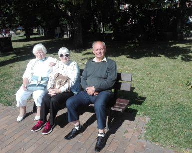 Seniorzy odpoczywają na ławce przed Muzeum Bursztynu.