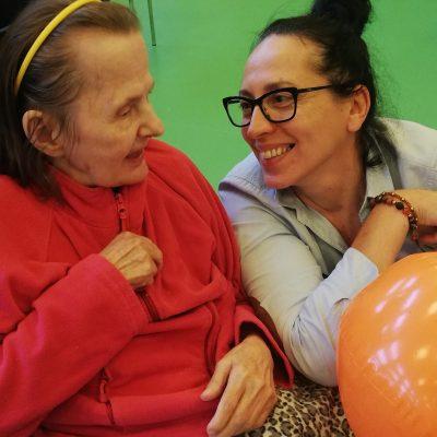 Na sali gimnastycznej obok siebie terapeutka Magdalena Poraj-Górska i seniorka. Uśmiechają się do siebie.