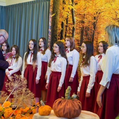 Dyrygent Andrzej Sitek i dziewczęta z chóru ASbeek występują na sali. Jesienna dekoracja, pomarańczowe kwiaty, dynie.