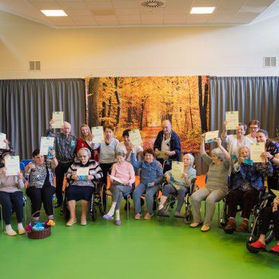 Na sali gimnastycznej dyrektorka Agnieszka Cysewska, pracownicy i seniorzy. Pozują do zdjęcia z dyplomami.