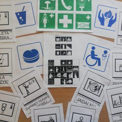 Na blacie kartki z różnymi symbolami. Pod niektórymi ilustrujące symbol napisy: toaleta, sala muzyki, gabinet terapii.