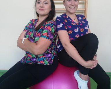Sala gimnastyczna. Fizjoterapeutki Paulina Winczura i Martyna Józefczyk siedzą na dużej, różowej piłce. Uśmiechają się.