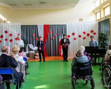 Sala udekorowana papierowymi czerwonymi makami. Na środku kierownik Arkadiusz Wanat i artyści. Przed nimi seniorzy.