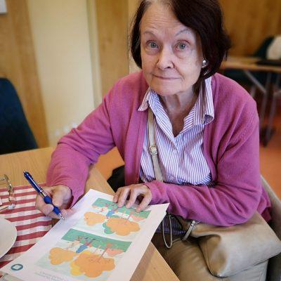 Seniorka siedzi przy stoliku. Uśmiecha się. W dłoni trzyma długopis. Przed nią na blacie kartka do ćwiczeń.