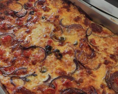 W prostokątnej blaszce upieczona pizza.