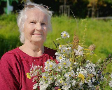 Uśmiechnięta seniorka stoi na zielonej trawie. W rękach trzyma bukiet polnych kwiatów. W tle zielone drzewa.