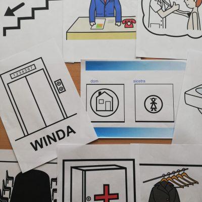 Na blacie kartki z różnymi symbolami, które służą do oznakowania przestrzeni i pomieszczeń w budynku.