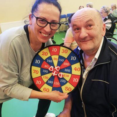 Terapeutka Magdalena Poraj-Górska i senior pozują z tarczą do gry w rzutki.