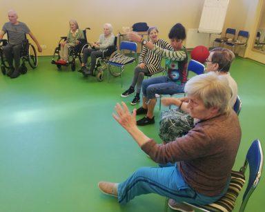 Sala gimnastyczna. Seniorzy i terapeutka Ania Rzepczyńska ćwiczą na siedząco.