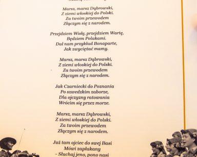 Kartka z tekstem polskiego hymnu. Tekst otoczony ramką, na dole strony mężczyźni i kobiety w strojach ludowych.