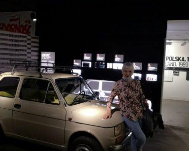 Muzeum Emigracji w Gdyni. Roześmiana seniorka pozuje do zdjęcia przy samochodzie marki 126 p, czyli maluchu.