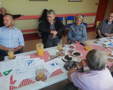 Przy stole seniorzy, kierownicy Ilona Gajewska i Arkadiusz Wanat. Na stole soki, czekolada, kartki z różnymi symbolami.