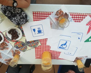 Na blacie kolorowe serwetki, dzbanek i szklanki z sokiem, czekolada na papierowym talerzyku, kartki z symbolami.
