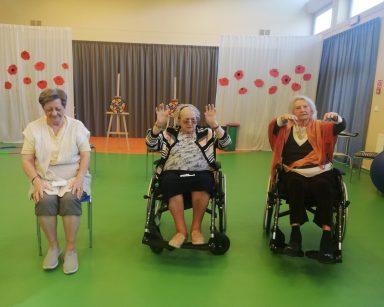 Sala gimnastyczna. Trzy seniorki w trakcie rozgrzewki na siedząco.